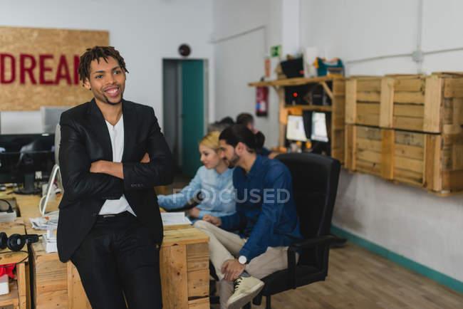 Портрет усміхнений бізнесмен, спираючись на столі і хтось дивитися вбік в офісі — стокове фото