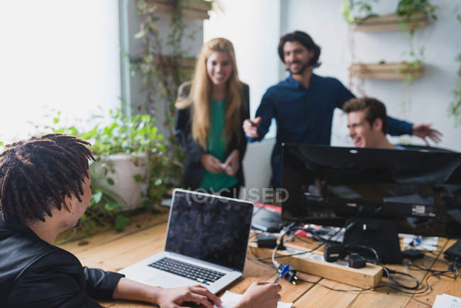 Office scene of workers laughing at workplace — Stock Photo