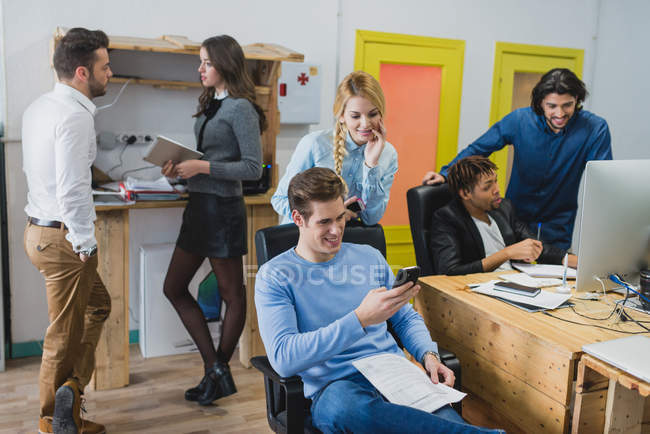 Office scene of team co-working and using gadgets at workplace in modern office — Stock Photo
