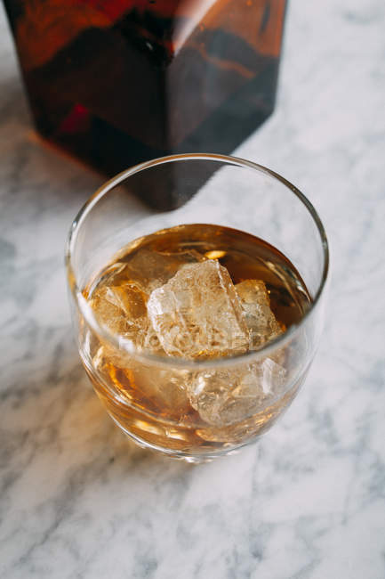 Glass of whiskey with ice — Stock Photo