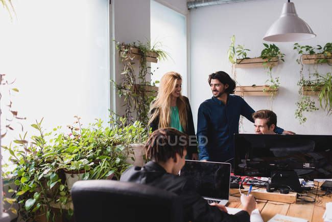 Office scene of workers communicating at workplace — Stock Photo