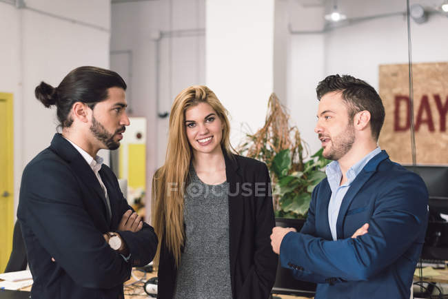 Woman looking at camera while men discussing in office. — Stock Photo