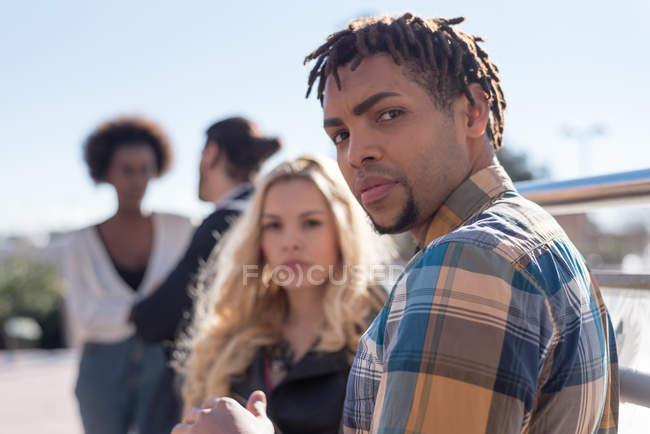 Человек, глядя через плечо на камеру во время общения с женщиной — стоковое фото