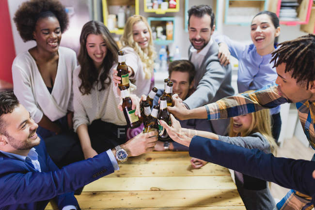 High angle view of people clanging bottles in  office while teambuilding — Stock Photo