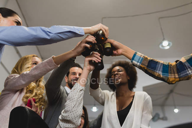 Low angle view of people clanging bottles in office while teambuilding — Stock Photo
