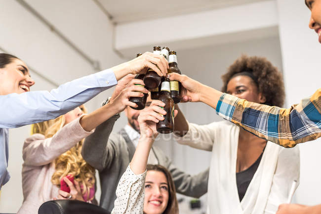 Portrait of people clanging bottles at office party — Stock Photo