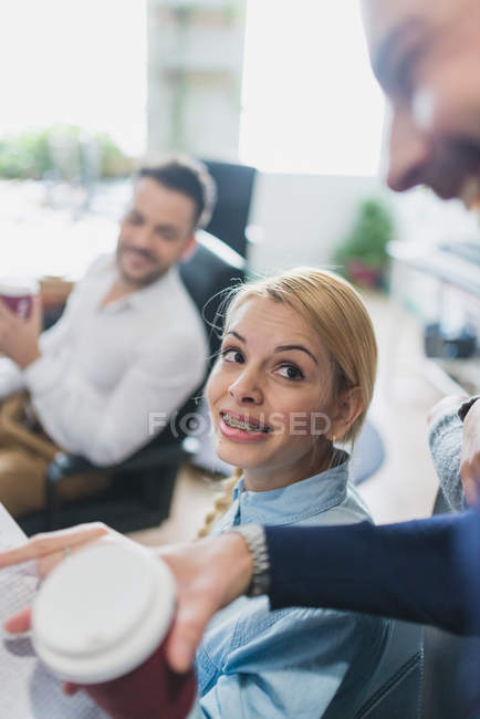 Portrait of blonde girl with brackets looking up at colleague at daily meeting — Stock Photo