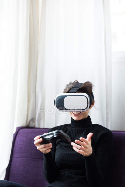 Front view of smiling brunette girl wearing virtual reality glasses and playing video game with gamepad — Stock Photo