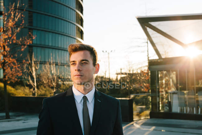 Confident Businessman in suit posing at street sunset — Stock Photo