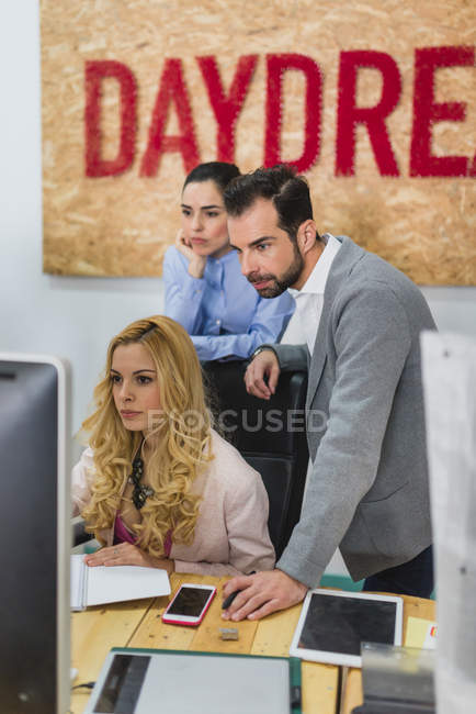 Portrait of entrepreneurs looking at colleagues screen at work place — Stock Photo