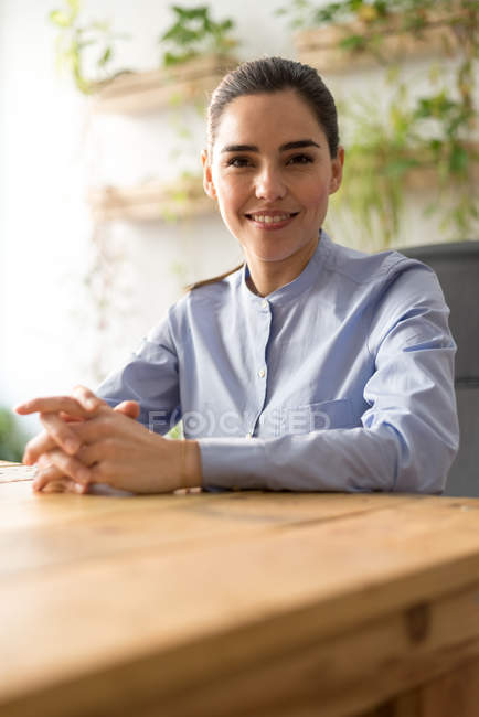 Smiling businesswoman sitting at workplace and looking at camera — Stock Photo