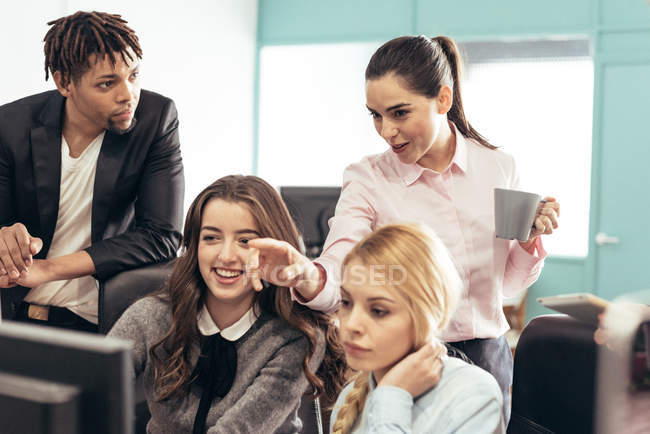 Cheerful business people discussing issue at workplace in office — Stock Photo