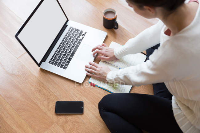 Top view of female student sitting on floor with mug of coffee and typing on laptop — Stock Photo