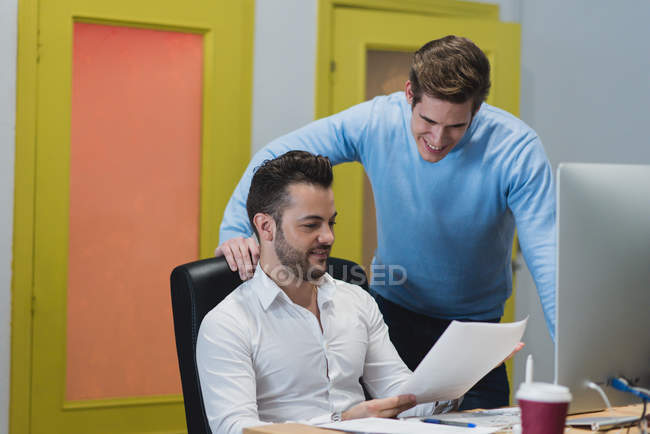 Portrait of smiling colleagues at desk and looking through documents in office. — Stock Photo