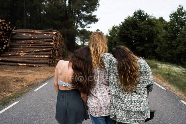 Three stylish girls sitting on rural road — Stock Photo