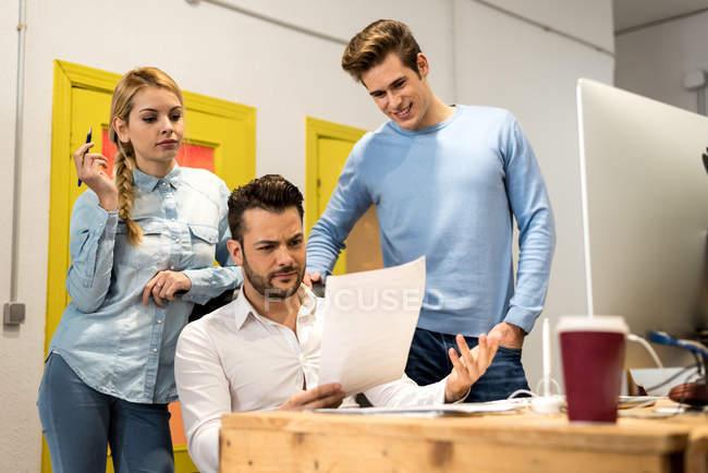 Porträt von Unternehmenskollegen, die am Arbeitsplatz Dokumente diskutieren — Stockfoto