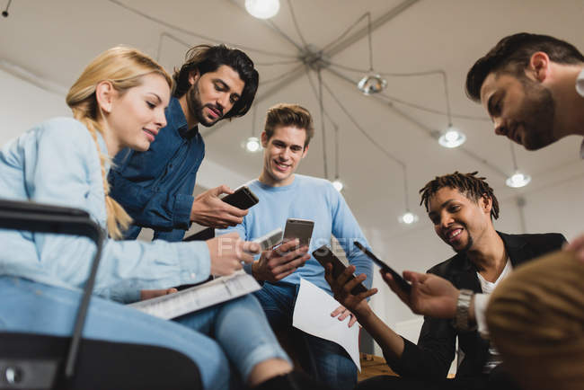 Low angle view of office workers looking into smartphones while meeting at office — Stock Photo