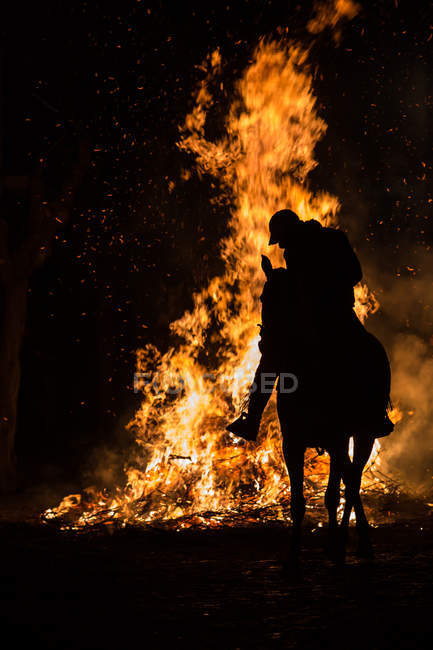 Silhouette of rider on horse on background of fire flames — Stock Photo