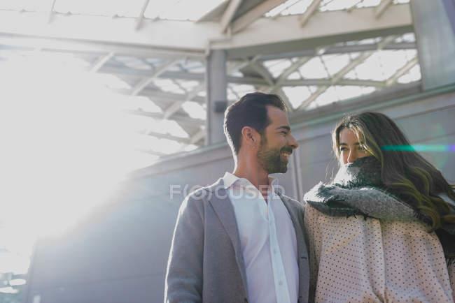 Angolo basso di coppia sorridente guardando a vicenda scena urbana — Foto stock
