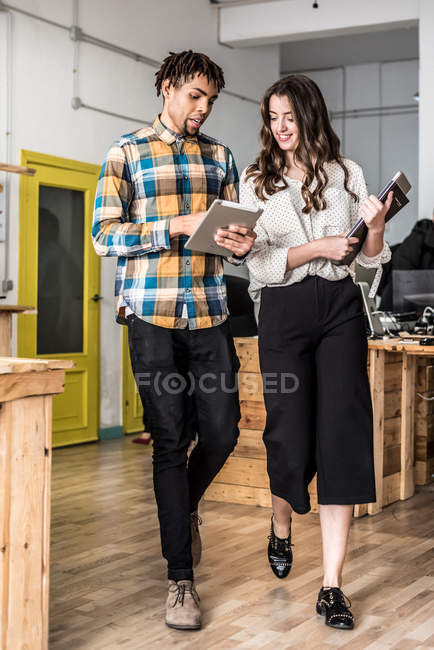 Cheerful colleagues walking in open-space office and discussing — Stock Photo