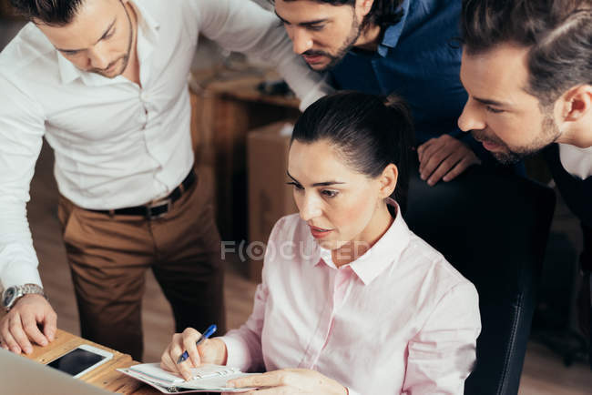 Business people bending over colleague writing in notebook — Stock Photo