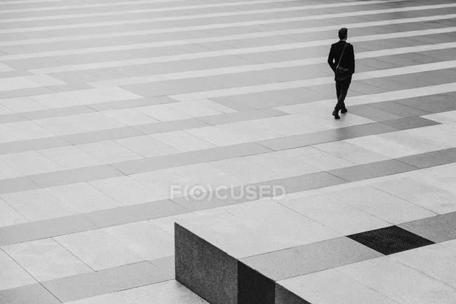 Empresário Caminhando através de um chão listrado — Fotografia de Stock