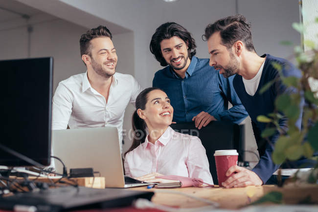 Smiling business people talking at colleague's workplace at office — Stock Photo