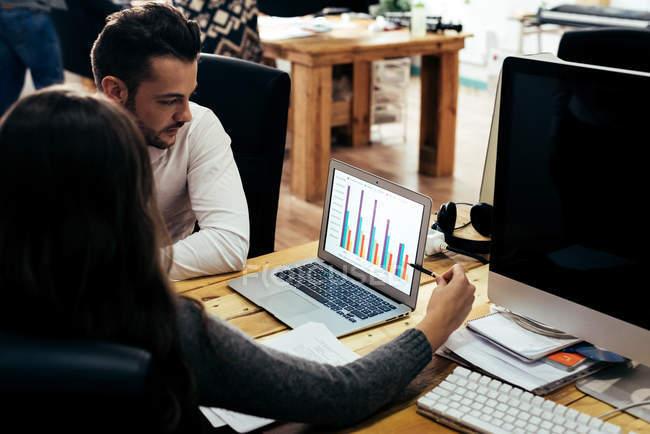 Люди говорили про графік звернено на екрані ноутбука. — стокове фото