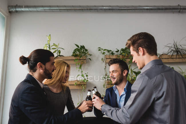 Side view of group of colleagues drinking beer after working time in office. — Stock Photo