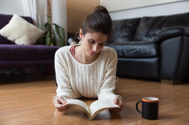 Фронтальний вид брюнетка дівчина лежав на підлозі і читання книги — стокове фото
