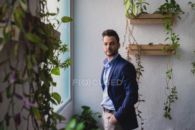 Портрет бізнесмен, носити костюм стоять біля вікна і, дивлячись на камеру — стокове фото