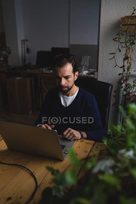 Portrait of man sitting at table and typing on laptop at office workplace — Stock Photo