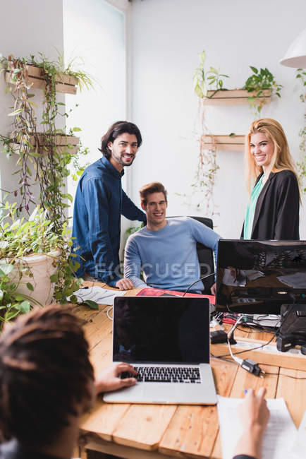 Portrait of smiling people looking at camera at workplace in office. — Stock Photo