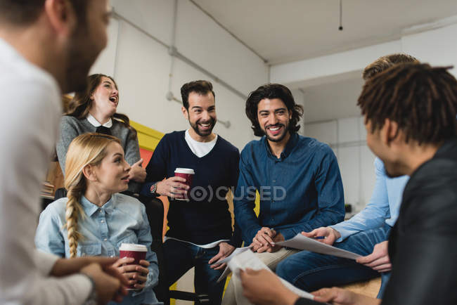 Portrait of smiling office team members talking at daily meeting — Stock Photo