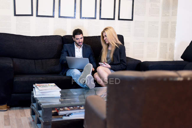 Веселий колег, сидячи на дивані в офіс і перегляду ноутбук. — стокове фото