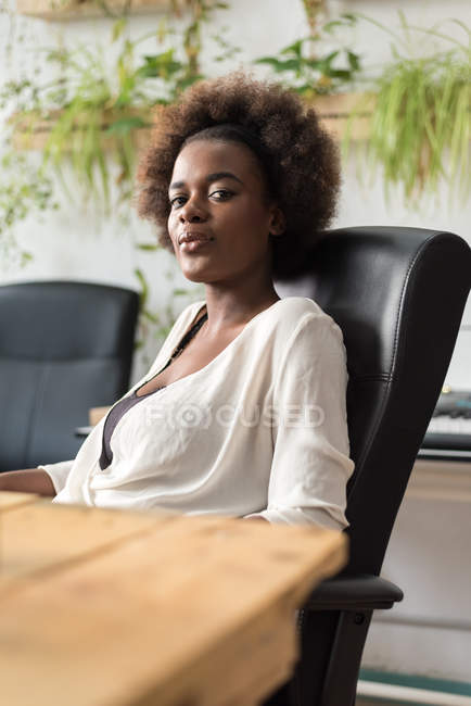 Thoughtful businesswoman sitting at workplace and looking at camera — Stock Photo