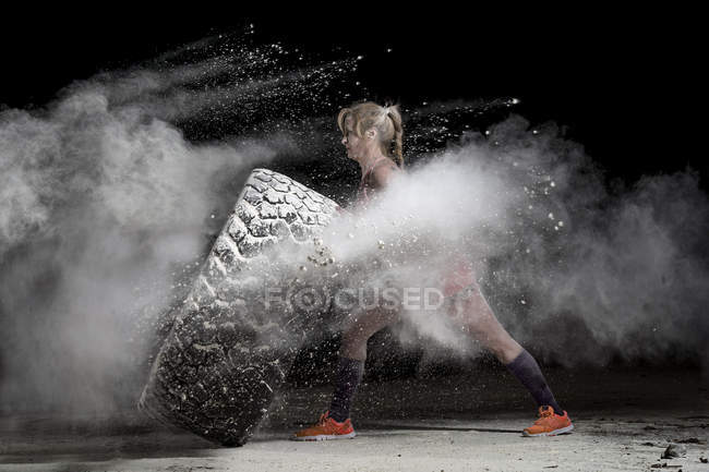 Woman pushing tire — Stock Photo