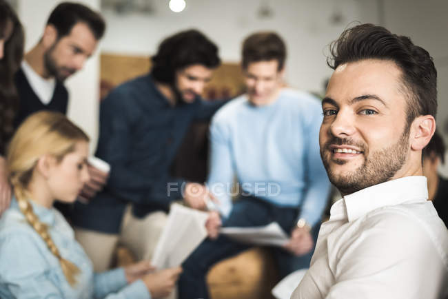 Cheerful man smiling at camera over group of people working in office — Stock Photo