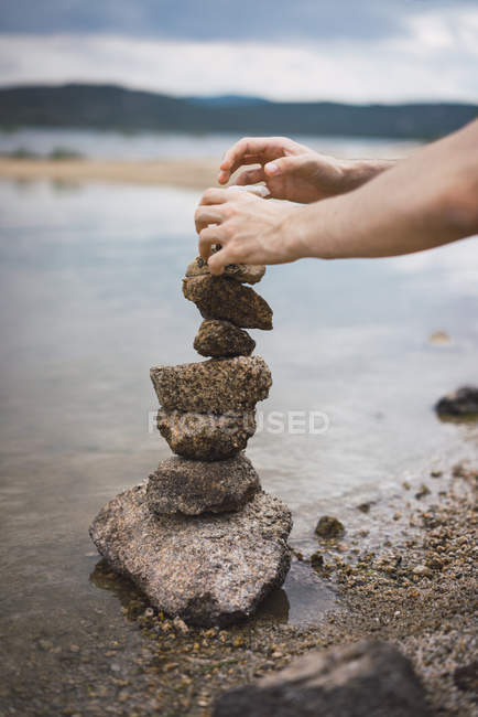 Hands stacking and balancing stones on lake shore. — Stock Photo