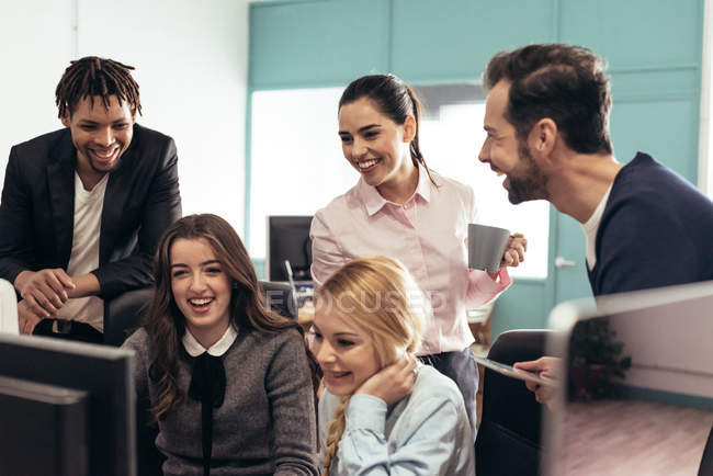Cheerful colleagues laughing at workplace in officer — Stock Photo