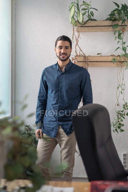 Portrait of businessman standing by window and looking at camera — Stock Photo