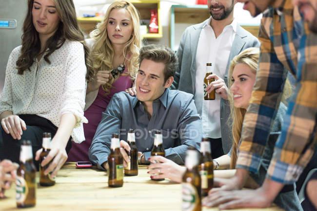 Equipo de la oficina sentado en la mesa y bebiendo cerveza - foto de stock