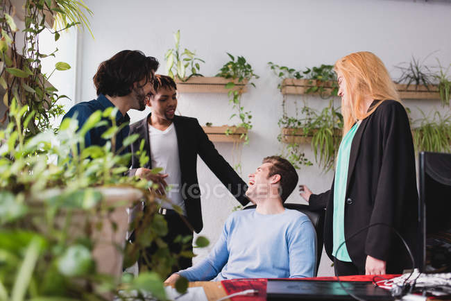 Portrait of laughing colleagues at workplace in office. — Stock Photo