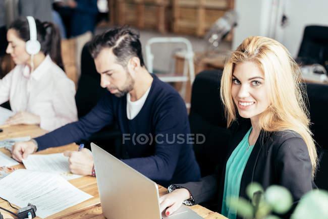 Mulher olhando para a câmera enquanto se senta no escritório com colegas — Fotografia de Stock