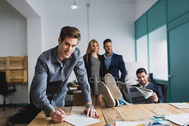 Porträt eines Mannes, der auf einem Tisch sitzt und Papiere über Büroangestellten unterschreibt — Stockfoto