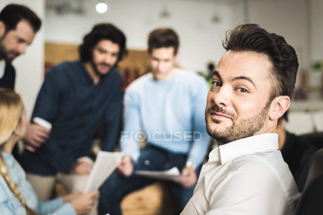 Smiling man looking at camera during brainstorm meeting at office — Stock Photo