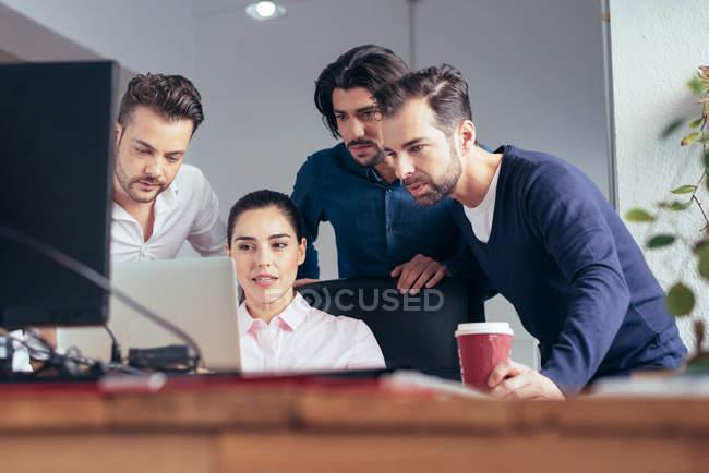 Бизнесвумен демонстрирует презентацию о коллегах по ноутбуку в офисе — стоковое фото