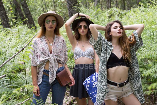 Three stylish girls posing in forest — Stock Photo