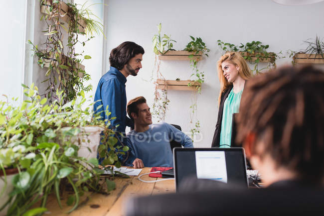 Over shoulder view of office workers talking while working in office. — Stock Photo