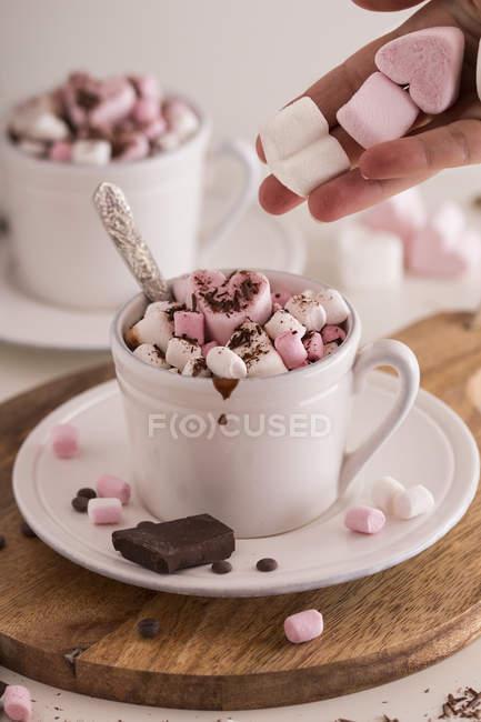Main de femme avec tasse de chocolat chaud — Photo de stock